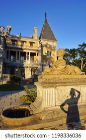 Massandra Palace, Yalta, Crimea, Russia. The royal palace with ancient windows, bell tower with spier, stone sculpture a lion with a girl's head on a pedestal and silhouette girl tourist photographer