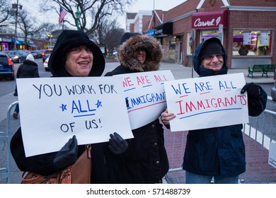 MASSAPEQUA PARK, NY - FEBRUARY 3: Three unidentified protesters hold pro-immigrant signs at a Travel Ban protest march outside of Rep. Peter King's office on February 3, 2017 in Massapequa Park.