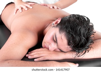 Masseur doing back massage on man body in the spa salon.