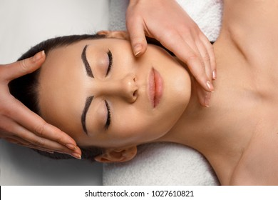 Masseur Doing Massage The Head Of  Woman In The Spa Salon