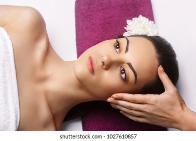 Masseur Doing Massage The Head Of  Woman In The Spa Salon.Facial treatment . Cosmetology,body  care.