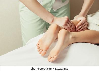 Masseur doing massage leg a little girl, close-up