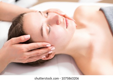 Masseur doing massage on face to beautiful girl closeup