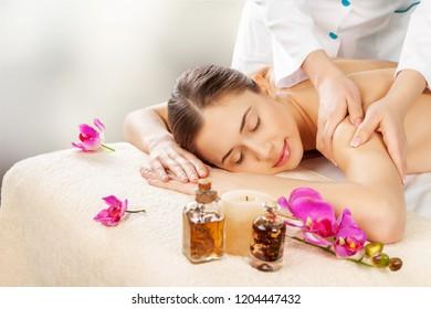 Masseur doing massage on woman body in