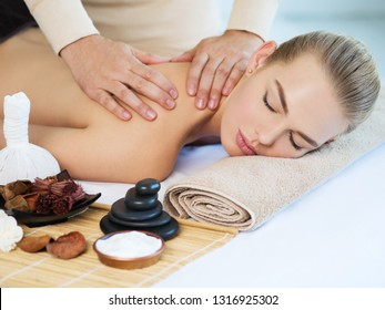 Masseur doing massage on woman body in the spa salon. Girl gets spa procedure. Beauty treatment concept.