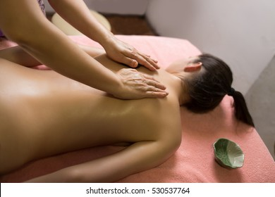 Masseur doing massage on woman back in the spa salon. top view
