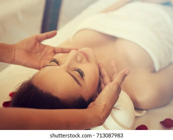 Masseur doing massage on woman body in the spa salon. Beauty treatment concept.Young woman brunette skin relaxing in spa.Young man and woman lying down on massage beds at Asian luxury spa.