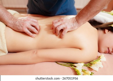 Masseur doing massage a woman in the salon