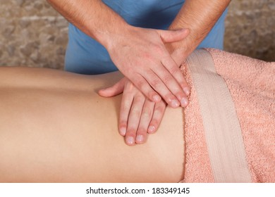 Masseur doing massage a young girl on a massage table