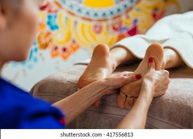 masseur doing reflexology, foot massage in exotic spa