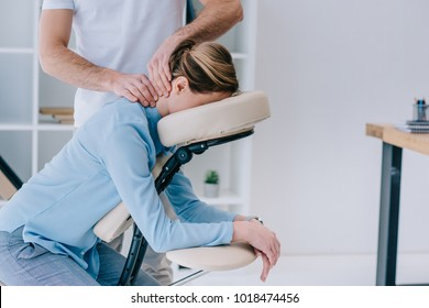 masseur doing seated neck massage for businesswoman
