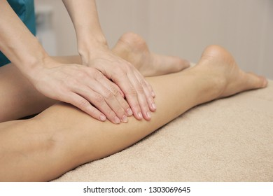 Masseur doing therapeutic foot massage for a woman, in a massage spa salon, close-up.
