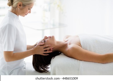 Masseur giving masage to young woman at spa