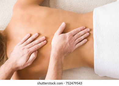 Masseur hands doing massage on young woman back in the spa beauty salon. Enjoying life. Relaxing day. Body care concept.