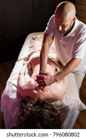 Masseur hands doing spine and back massage, neck and hand. Relaxed patient enjoys. Man hands massaging female. Spa centre concept. close-up