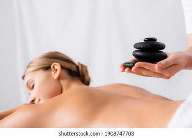masseur holding hot stones near client on blurred background