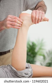 Masseur holding a tendon in his office