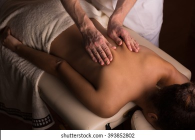 Masseur kneading the muscles on woman's back during therapeutic massage