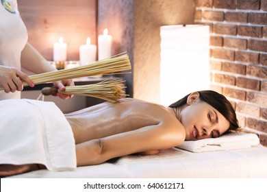 Masseur makes massage to young girl. Woman having bamboo stick massage at day spa