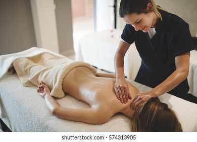 Masseur massaging back of female in spa resort