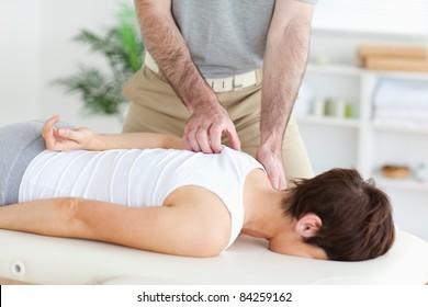 Masseur massaging a brunette woman's shoulder in a room