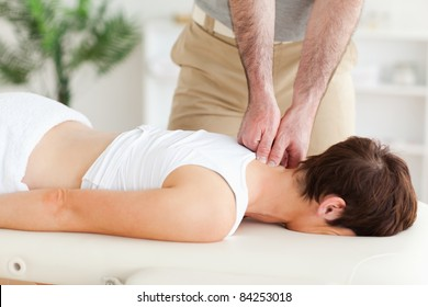A masseur is massaging a customer's neck in his surgery