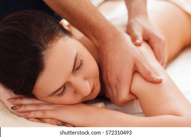 Masseur massaging female shoulders closeup. Portrait of young woman enjoying relaxing massage. Beauty, relax, rest, health care, body, pleasure, stress relief concept