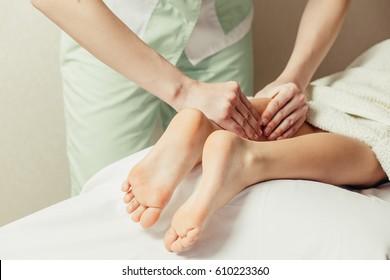 Masseur massaging little girl foot.