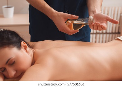 Masseur massaging woman with aroma oil. Side view on nude brunette relaxing at oriental spa procedures, free space. Beauty, rest, health care, pleasure, body concept