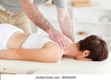 A masseur is massaging a woman's neck
