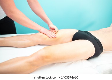 A masseur and physiotherapist quadriceps massage to an athlete