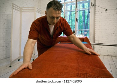 Masseur preparing massage couch covering it with blanket. Horizontal shot