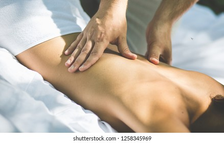 Masseur  removes all stress. Massage at nature really relaxing. Close up image.