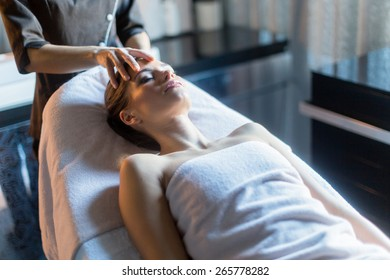 Masseur treating face of a beautiful, young woman lying on the massage table