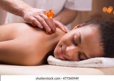 Masseur using accessories while giving massage to a young woman