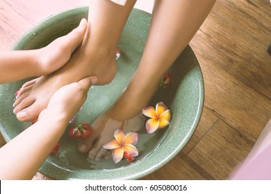 Masseur washing woman's foot or feet in ceramic bowl for cleaning dusty and smell before doing body oil massage aromatherapy, take care foot healthy - Spa and massage concept