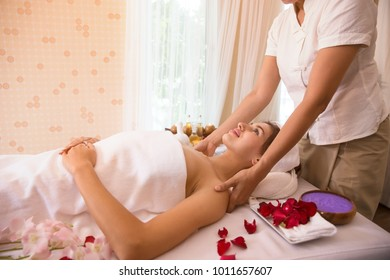 masseur which rejuvenating and doing massage on female shoulder in the beauty  center of salon