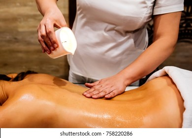 Masseur woman drips wax from a candle on the back of the young girl, rubbing massage oil. Relaxation before the holidays