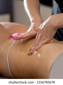 masseuse applies honey on the body of a woman on a massage table. Honey massage in the spa