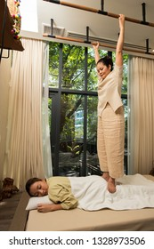 Masseuse body massage Mix races Caucasian Asian woman by stand walk on legs, back, shoulder to weight pressure on pain point, Thai Massage traditional stretching techniques