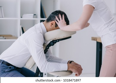 masseuse doing seated head massage for businessman