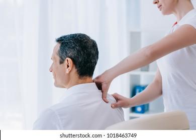 masseuse doing seated shoulder massage for businessman