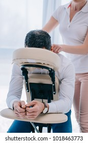 masseuse doing shoulders massage on seat at office