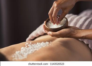 Masseuse mains faisant un massage sur le dos de la femme au salon de beauté. Un thérapeute de beauté déverse un gommage au sel sur une femme au spa. Concept de soin et de soin de la peau.