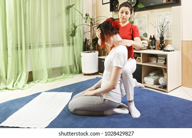 Masseuse makes young woman yumeiho neck massage. This oriental therapy is a complex set of manual procedures and physical exercises. Horizontal shot