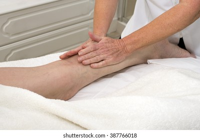 A masseuse massaging a clients leg