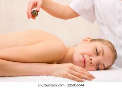Masseuse pouring massage oil woman's back