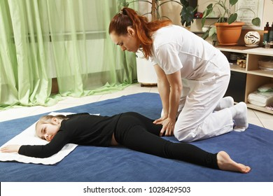 Masseuse pressing on child hip with fingers during yumeiho massage. This oriental therapy is a complex set of manual procedures and physical exercises. Horizontal shot
