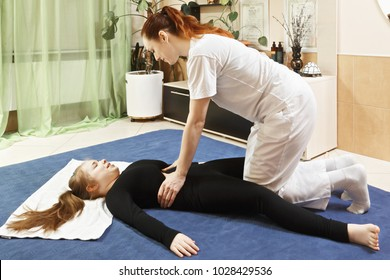Masseuse pressing on girl stomach during yumeiho massage. This oriental therapy is a complex set of manual procedures and physical exercises. Horizontal shot