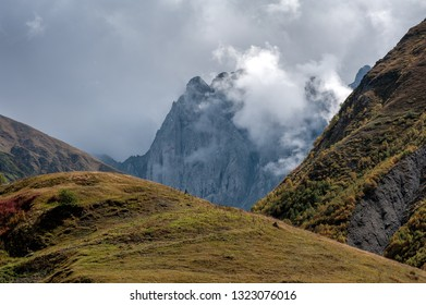 The massif of Chaukhi between green grass covered slopes